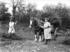 A black and white photograph showing three women from the Women's Land Army at work on a farm.