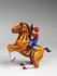 A photograph showing a clockwork toy,with a horse and rider who is a cowboy.